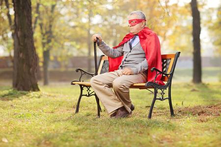 gente loca: Mayor triste en traje de superh�roe sentado en el parque en un banco de madera