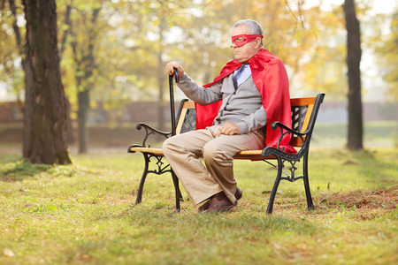 mad: Sad senior in superhero outfit sitting in park on a wooden bench
