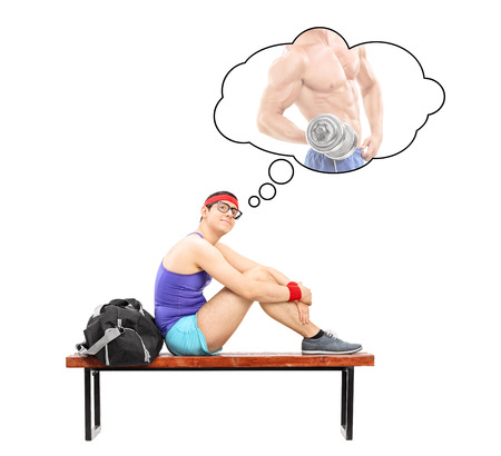 imagining: Nerdy guy imagining himself as a bodybuilder seated on a bench isolated on white background Stock Photo