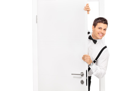 man behind: Elegant young guy posing behind a door isolated on white background Stock Photo