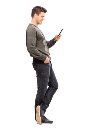 phone isolated: Full length portrait of a young man texting on his cell phone isolated on white background