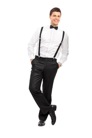 white man: Full length portrait of a handsome guy with suspenders and bow-tie leaning against a wall isolated on white background Stock Photo