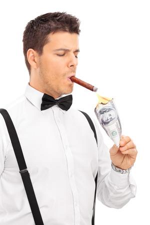 Vertikale Schuss von einem reichen Mann zündet sich eine Zigarre mit brennenden Dollar isoliert auf weißem Hintergrund