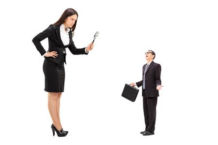 supervisión: Empresaria gigante observando un pequeño hombre de negocios a través de una lupa aislada en el fondo blanco