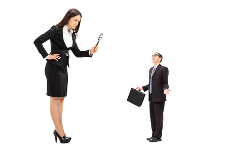 supervision: Giant businesswoman observing a tiny businessman through a magnifying glass isolated on white background