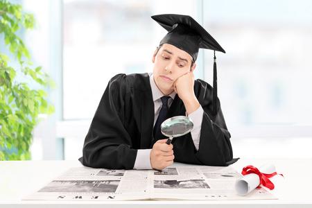 puesto de trabajo: Estudiante en busca de un trabajo en un peri�dico en su casa con una lupa