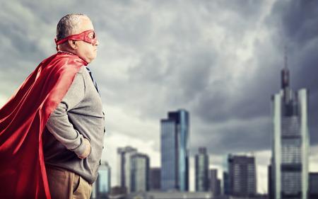 Senior superheld staande in de voorkant van een donkere stad