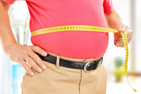 Close-up on a man measuring his belly at home