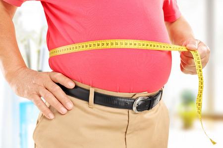 obesidad: Primer plano de un hombre que mide su vientre en casa