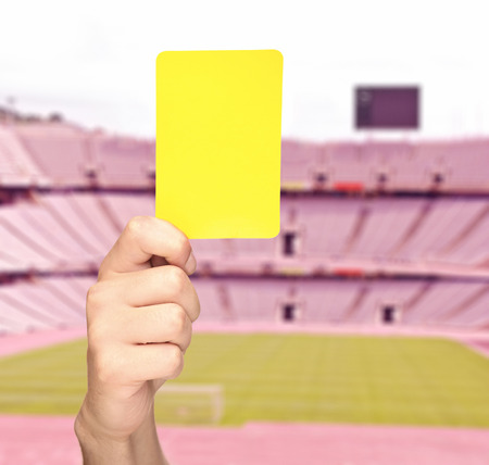 Hand showing a yellow card in front of an empty stadium shot with tilt and shift lens Stock Photo