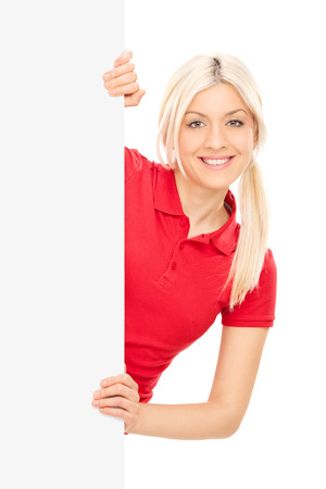 woman from behind: Young blond woman posing behind a blank panel isolated on white background