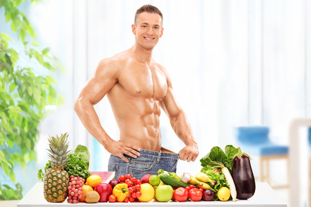 Attractive male posing behind a table with vegetables and fruit at home
