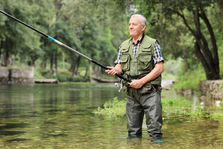 man fishing: Alegre pesca pescador madura en un río al aire libre