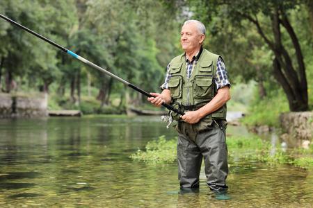 hombre pescando: Alegre pesca pescador madura en un r�o al aire libre