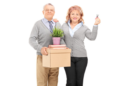 relocating: Mature couple holding moving boxes and keys isolated on white background Stock Photo