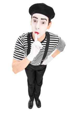 shush: Mime artist holding a finger on his lips isolated on white background