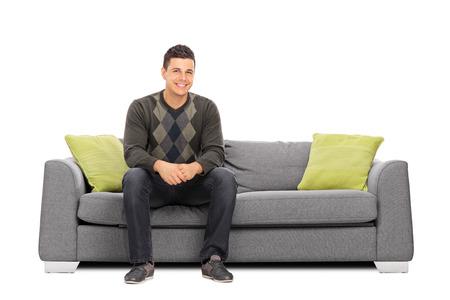 明朗快活な青年は、白い背景で隔離のモダンなソファの上に座って