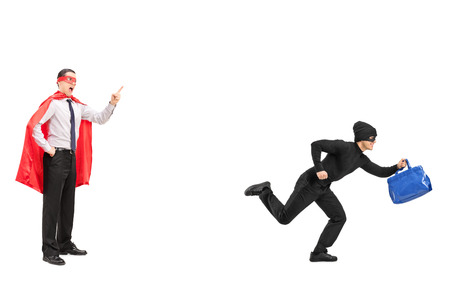 Full length portrait of a superhero chasing a burglar isolated on white background
