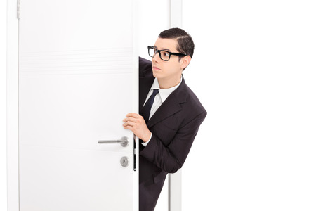 baffled: Curious young businessman looking through a door isolated on white background