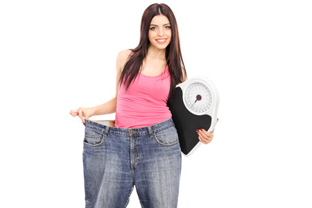 oversized: Girl in oversized jeans holding a weight scale isolated on white background