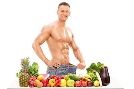 Handsome man posing behind a table with vegetables isolated on white background photo