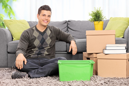 Man seated on the floor by a bunch of boxes at home photo