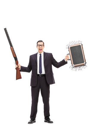 Full length portrait of an angry businessman holding a rifle and a bag full of money isolated on white background photo