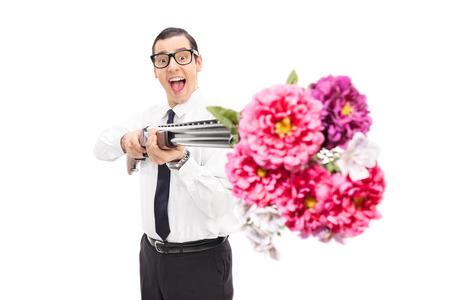hombre disparando: Gozosos hombre fotografiar flores de una escopeta aislados sobre fondo blanco