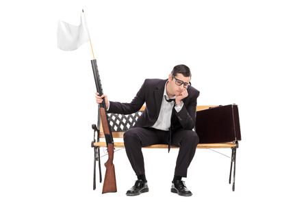 it is isolated: Businessman holding rifle with white flag on it isolated on white background