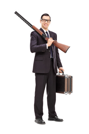 Full length portrait of a businessman holding a rifle and a briefcase isolated on white background photo