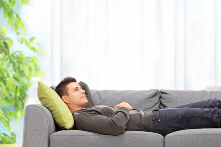 imagining: Relaxed young man lying on a sofa at home Stock Photo