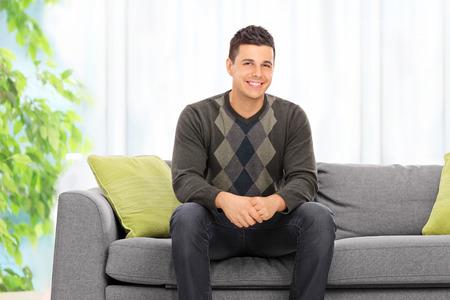 hombre sentado: Presentación del hombre joven sentado en un sofá en casa