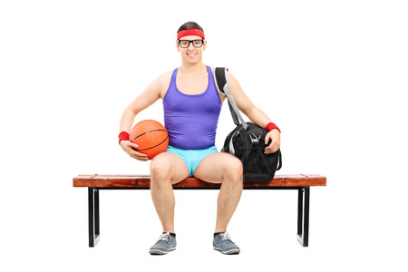 nerdy: Nerdy athlete holding a basketball seated on a bench isolated on white background