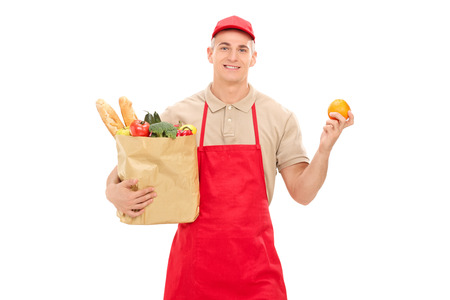 market vendor: Retail worker holding an orange and a grocery bag isolated on white background Stock Photo
