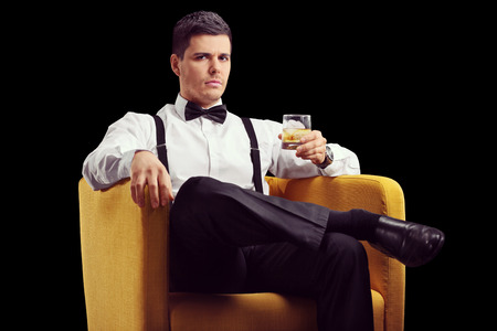 bourbon: Serious man sitting in an armchair and drinking whiskey on black background