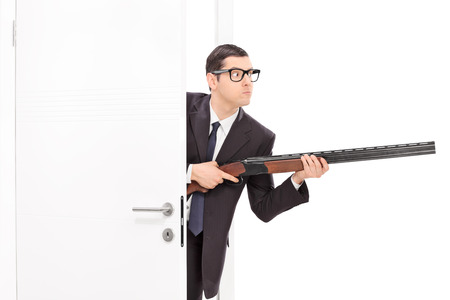 suspicious: Businessman holding rifle and entering a room isolated on white background Stock Photo