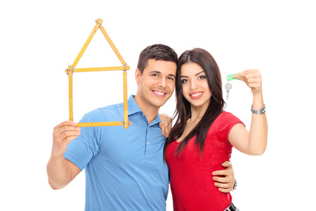 happy couple white background: Couple holding tape measure in form of house and key isolated on white background