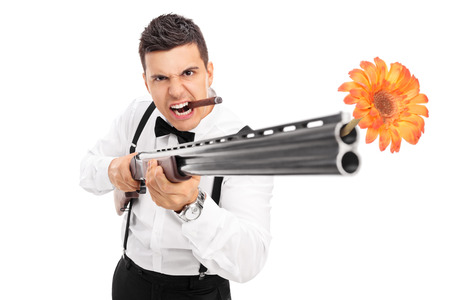 harmless: Angry guy shooting flowers from a rifle isolated on white background Stock Photo