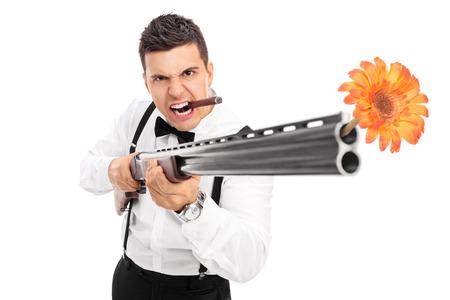 hombre disparando: Guy fotografiar flores Angry desde un rifle aislados en el fondo blanco Foto de archivo