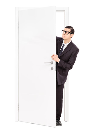 Full length portrait of a businessman peeking through an opened door isolated on white background