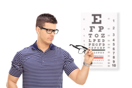 eye chart: Man trying on glasses in front of an eye chart isolated on white background