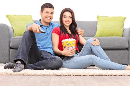 pareja viendo tv: Joven pareja viendo la televisi�n sentado en el suelo aislado en el fondo blanco Foto de archivo
