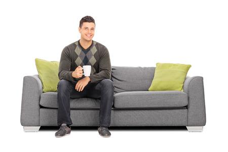 hombre sentado: Hombre joven que sostiene una taza de café sentado en el sofá aislado sobre fondo blanco Foto de archivo