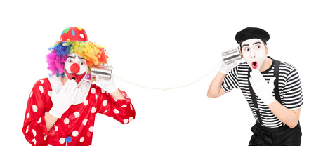 tin can phone: Clown and a mime artist talking through a tin can phone isolated on white background