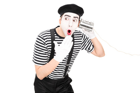 Surprised mime artist listening through a tin can phone isolated on white background photo