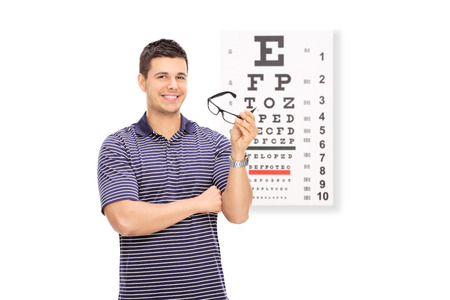 eye chart: Young guy holding glasses in front of an eye chart isolated on white background Stock Photo