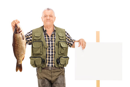 Smiling mature fisherman holding a big fish next to a panel isolated on white background photo
