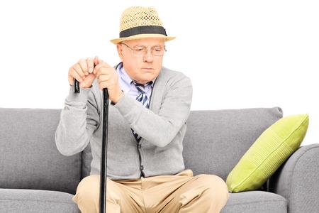 cane sofa: Worried senior gentleman sitting on a sofa isolated on white Stock Photo