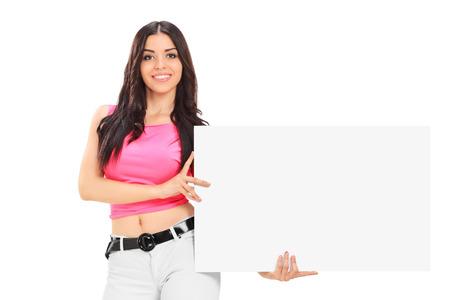 Jonge vrouw die een leeg wit karton houdt dat op witte achtergrond wordt geïsoleerd