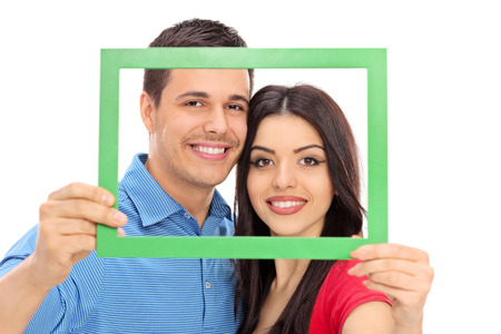 Couple posing behind a green picture frame isolated on white background photo